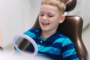A little boy looks at his teeth in a mirror after receiving pediatric dentistry in Bellaire, TX