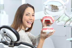 a woman with Impacted Teeth holding a mouth model